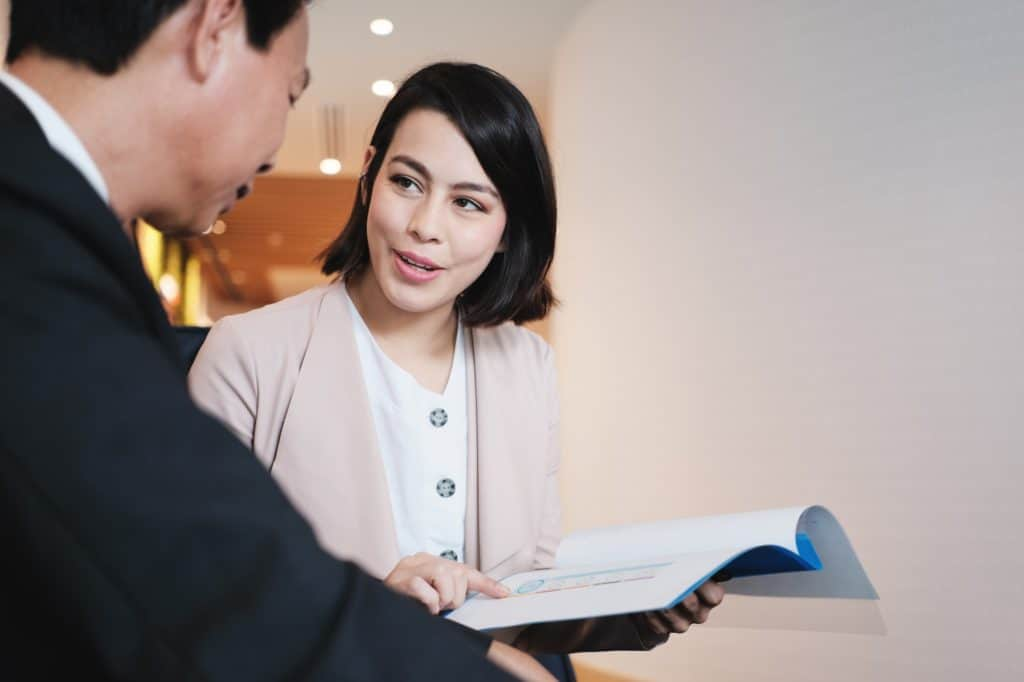 Investment Plan Agent Showing Documents To Asian Customer In Bank