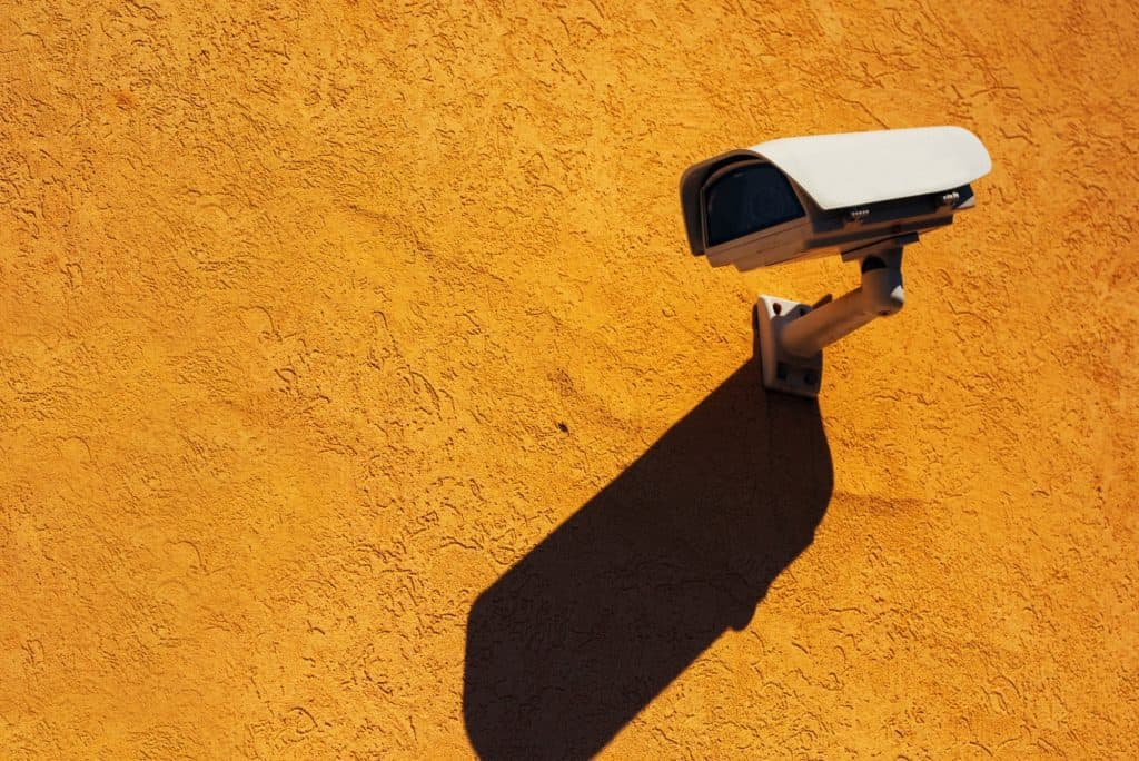 Security camera on yellow wall